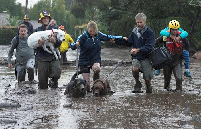 <p>Emergency personnel evacuate local residents and their dogs through flooded waters after a mudslide in Montecito, Calif., Jan. 9, 2018. (Photo: Kenneth Song/Santa Barbara News-Press via Reuters) </p>