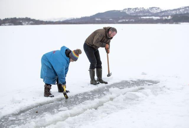 Al and Alice Goodridge, from Newtonmore, use a sledgehammer and an axe to create a channel in the ice in Loch Insh, in the Cairngorms National Park, for Alice to swim in
