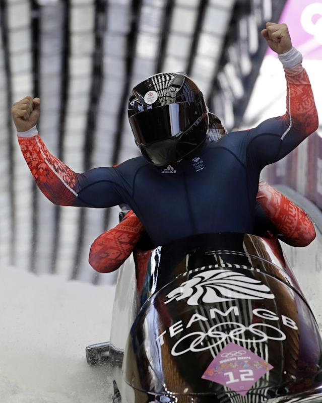 The team from Great Britain GBR-1, with John James Jackson, Stuart Benson, Bruce Tasker and Joel Fearon, react after their final run during the men's four-man bobsled competition final at the 2014 Winter Olympics, Sunday, Feb. 23, 2014, in Krasnaya Polyana, Russia. (AP Photo/Dita Alangkara)