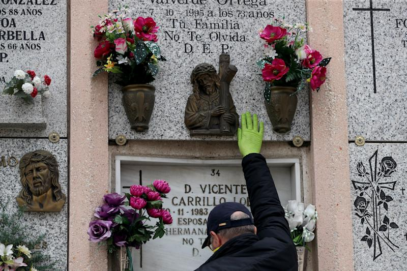 Carolina Navarro's son touches the headstone of his parents' niche with a protective glove after the burial of his mother at a cemetery in Madrid, Spain, Tuesday. REUTERS/Susana Vera