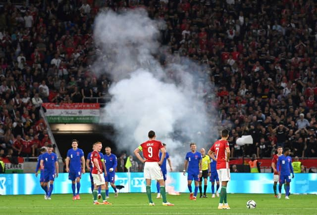 Players wait after a flare was thrown on to the pitch following England's third goal