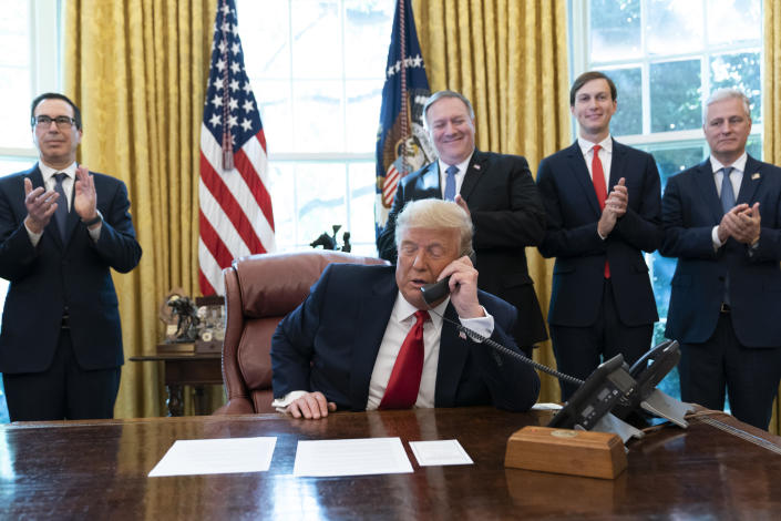 FILE - In this Oct. 23, 2020 file photo, President Donald Trump talks on a phone call with the leaders of Sudan and Israel, as Treasury Secretary Steven Mnuchin, left, Secretary of State Mike Pompeo, White House senior adviser Jared Kushner, and National Security Adviser Robert O'Brien, applaud in the Oval Office of the White House, in Washington. The U.S. Embassy in Khartoum said the administration removed Sudan from the U.S. list of state sponsors of terrorism, a move that could help the African country get international loans to revive its battered economy and end its pariah status. The embassy said in a Facebook post that the removal of Sudan from the list is effective as of Monday, Dec. 14, 2020. Delisting Sudan from the state sponsors blacklist is a key incentive for the Sudanese government to normalize relations with Israel. (AP Photo/Alex Brandon, File)