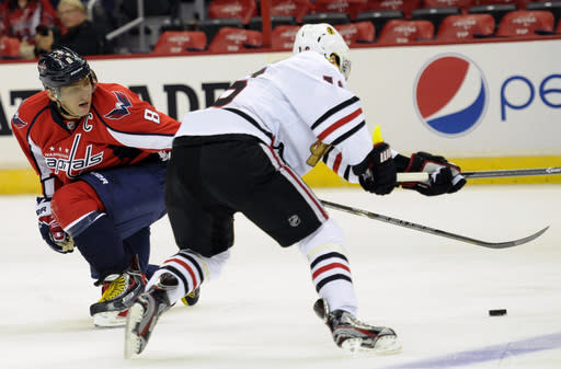 Washington Capitals right wing Alex Ovechkin (8), of Russia, reaches for the puck against Chicago Blackhawks center Marcus Kruger, right, of Sweden, during the first period an NHL preseason hockey game on Friday, Sept. 20, 2013, in Washington. (AP Photo/Nick Wass)