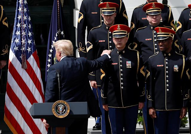 "U.S. President Donald Trump reaches out to a member of the United States Army Chorus as he departs his ""celebration of America"" event on the South Lawn of the White House in Washington, U.S., June 5, 2018. The event was arranged after Trump canceled the planned visit of the Super Bowl champion Philadelphia Eagles to the White House. REUTERS/Kevin Lamarque"