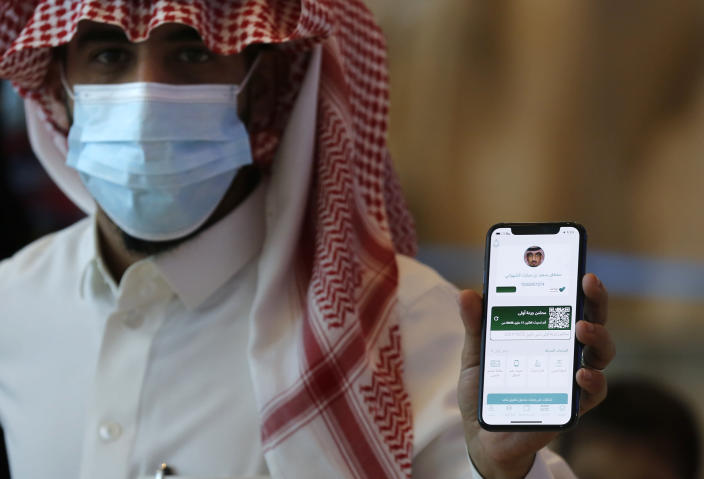 Saudi passenger, Sultan Saeed Al-Shahrani, shows his vaccination certificate on his mobile phone, at a checkpoint at King Abdulaziz International Airport in Jiddah, Saudi Arabia, Monday, May 17, 2021. Vaccinated Saudis will be allowed to leave the kingdom for the first time in more than a year as the country eases a ban on international travel that had been in place to try and contain the spread of the coronavirus and its new variants. (AP Photo/Amr Nabil)