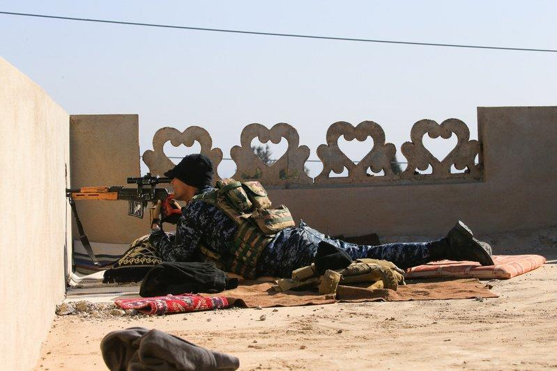 A sniper from Iraq's Federal Police force takes aim at Islamic State positions from the roof of a house on the frontline in Albu Saif, south of Mosul. REUTERS/Alaa Al-Marjani