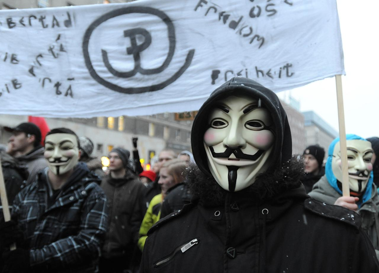 Internet activists wearing masks protest against the international copyright agreement ACTA , the Anti-Counterfeiting Trade Agreement, in front of the European Parliament office in Warsaw, Poland, Tuesday, Jan. 24, 2012. The Polish government plans to sign the agreement and Poland's support for ACTA has sparked days of protest, including attacks on government sites, by groups who fear it could lead to online censorship. (AP Photo/Alik Keplicz)