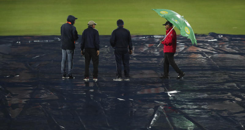 A match curator, left, inspects the field during the first Twenty20 cricket match between India and Sri Lanka in Gauhati, India, Sunday, Jan. 5, 2020. The match delayed for the rain. (AP Photo/Anupam Nath)