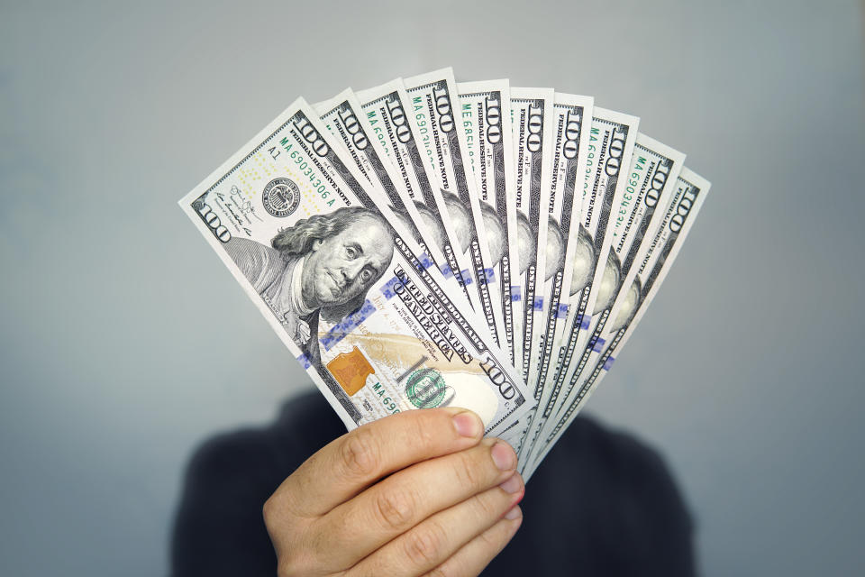 Hands holding dollar cash. 1000 dollars in 100 bills in a man's hand close-up on a dark background.