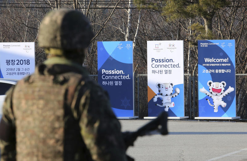 Posters showing the 2018 Pyeongchang Winter Olympic mascot are displayed as a South Korean army soldier stands guard at the Unification Observation post in Goseong, near the border with North Korea, South Korea, Friday, Jan. 19, 2018. The rival Koreas agreed Wednesday to form their first unified Olympic team and have their athletes parade together for the first time in 11 years during the opening ceremony of next month's Winter Olympics in South Korea, officials said. (AP Photo/Ahn Young-joon)