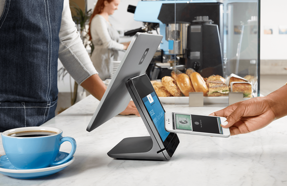 A person paying with an iPhone at a Square Register