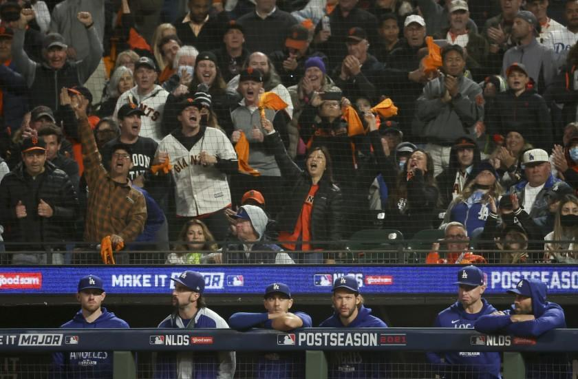 Giants fans cheer behind the Dodgers' bench after a fifth-inning strikeout by AJ Pollock at Oracle Park on Oct. 8, 2021.