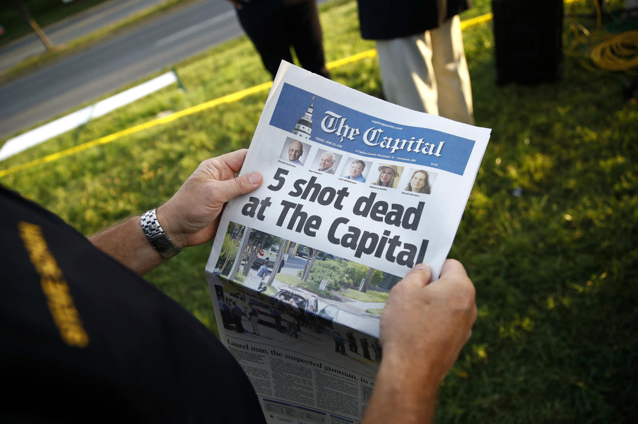 A man holds a copy of the Capital Gazette near the newspaper's office in Annapolis, Md., on Friday, the day after a mass shooting there. (AP Photo/Patrick Semansky)