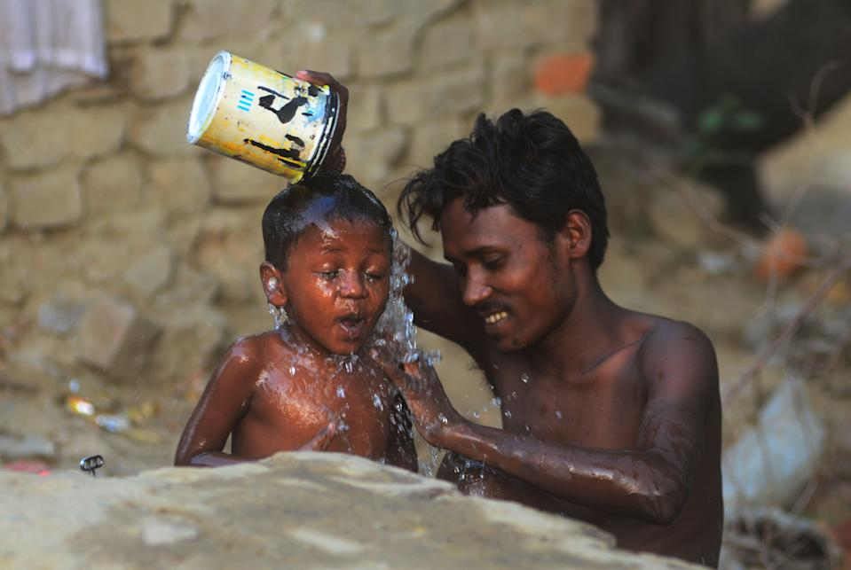 An indian man gives a bath to his kid during a hot day in the outskirts of Allahabad on June 5, 2019 . Temperatures passed 50 degrees Celsius (122 Fahrenheit) in northern India as an unrelenting heatwave triggered warnings of water shortages and heatstroke.(Photo by Ritesh Shukla/NurPhoto via Getty Images)