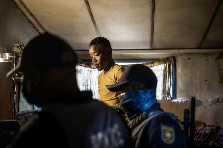 Police go through a home at the Nguni Hostels in the Johannesburg suburb of Vosloorus, looking for goods looted from a nearby shopping mall