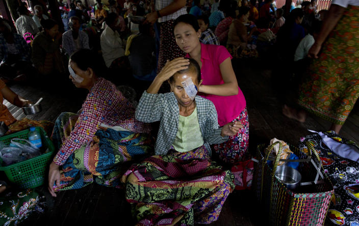 """In this Oct. 23, 2013 photo, a patient with an eye patch who spent the night on the floor of a Buddhist monastery following a simple operation to remove a cataract, receives help to comb her hair in Bago, Myanmar. Five decades of isolation, military rule and woeful health care have left Myanmar with one of the highest rates of blindness in the region. Now the veil of darkness is starting to lift, thanks to an """"assembly line"""" surgical procedure that allows cataracts to be removed safely, without stitches, through two small incisions. (AP Photo/Gemunu Amarasinghe)"""