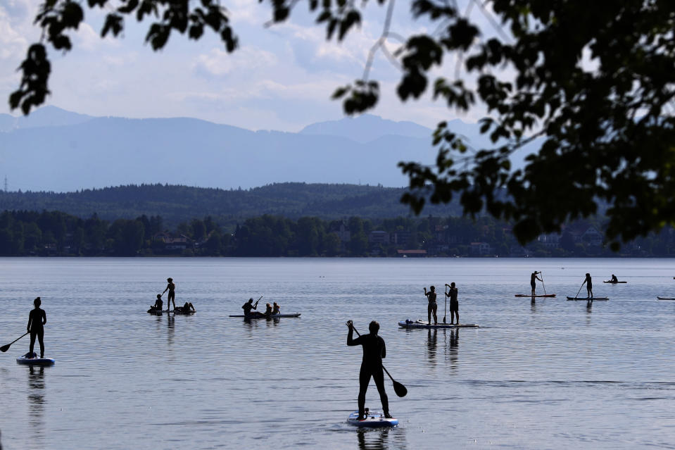 Stand-up paddlers on lake 'Starnberger See' in front of the Alps and Germany's highest mountain 'Zugspitze' (2962 meters) near Seeshaupt, Germany, Sunday, May 10, 2020. (AP Photo/Matthias Schrader)