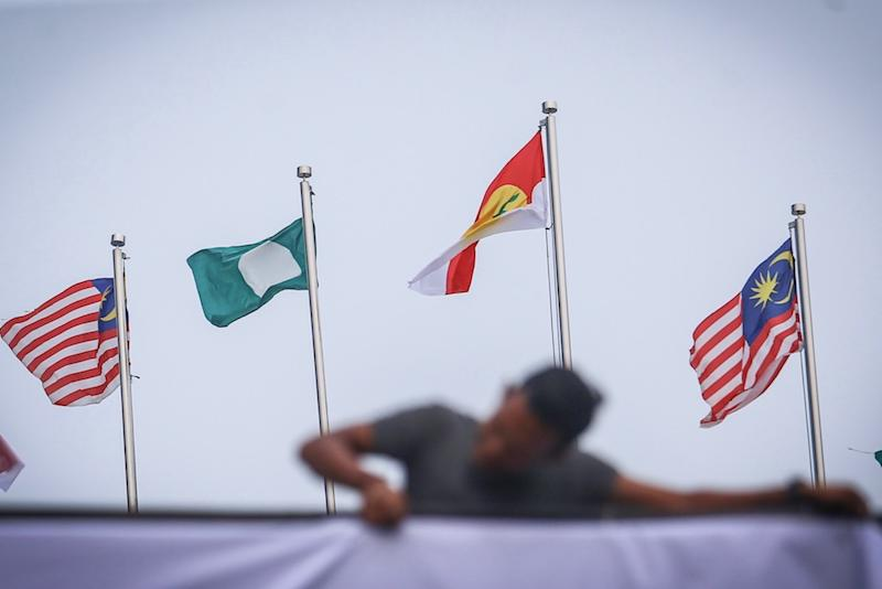 A man hangs Umno, PAS and Malaysia flags at Putra World Trade Centre in Kuala Lumpur September 12, 2019, ahead of the Muslim Unity Rally. — Picture by Hari Anggara