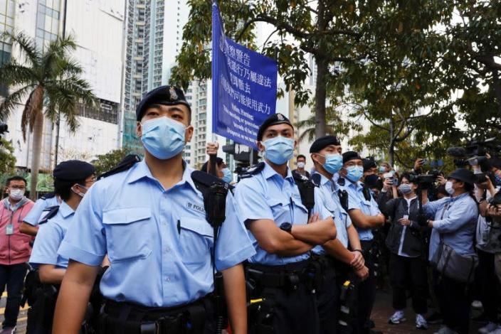 Police raise a warning flag as they try to disperse supporters of pro-democracy activists outside West Kowloon Magistrates' Courts, in Hong Kong
