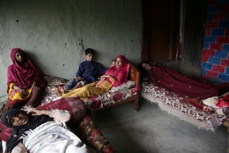 Women and a boy, who according to family were injured after a cluster bomb that looked like a toy exploded in the hands of a child at home, lay on beds in village Jabri, in Neelum Valley