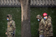 Construction workers wearing face masks to protect against the spread of the coronavirus walk along a street during a snowy morning in Beijing, Tuesday, Jan. 19, 2021. A Chinese province near Beijing grappling with a spike in coronavirus cases is reinstating tight restrictions on weddings, funerals and other family gatherings, threatening violators with criminal charges. (AP Photo/Mark Schiefelbein)