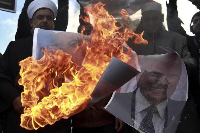<p>Palestinians burn posters of Israeli Prime Minister Benjamin Netanyahu and President Donald Trump, during a protest against the U.S. decision to recognize Jerusalem as Israel's capital, in Gaza City Thursday, Dec. 7, 2017. (Photo: Khalil Hamra/AP) </p>