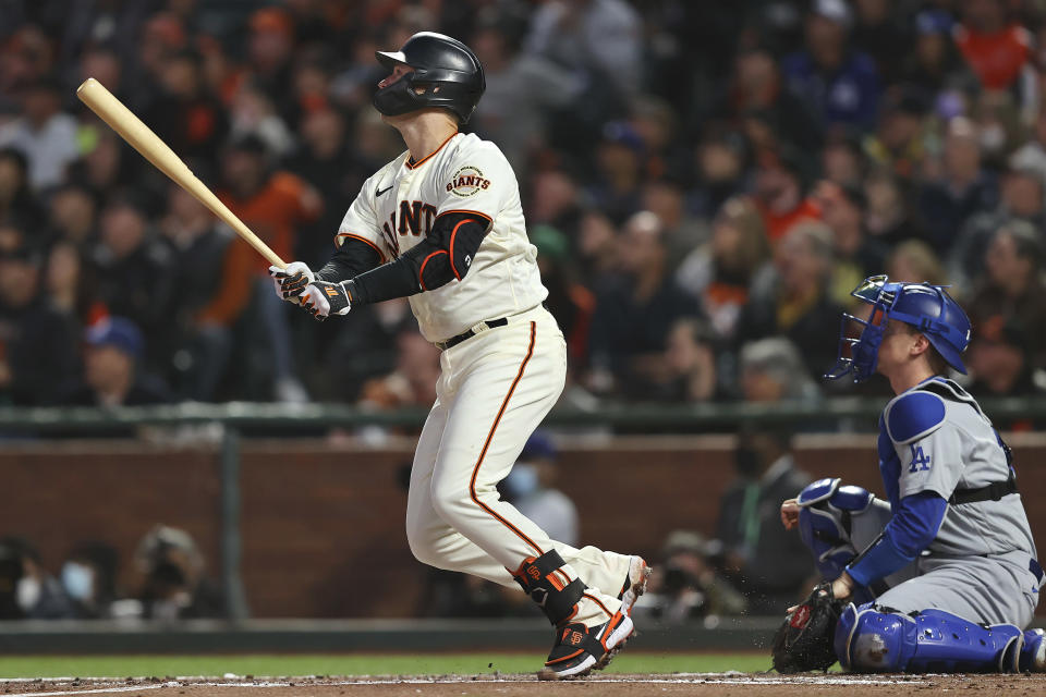 San Francisco Giants' Buster Posey, left, watches his two-run home run in front of Los Angeles Dodgers catcher Will Smith during the first inning of Game 1 of a baseball National League Division Series Friday, Oct. 8, 2021, in San Francisco. (AP Photo/John Hefti)