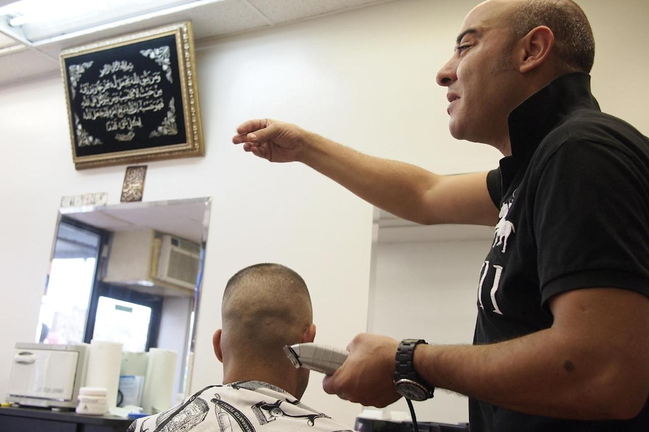 In this photo taken Sept. 2, 2011, Amine Darhbach, a U.S. citizen from Morocco, is interviewed as he cuts hair at his barber shop in the Astoria neighborhood in the Queens borough of New York. His shop had been under scrutiny by the New York Police Department as part of a secret program to gather intelligence on the city's Moroccan population. The New York Police Department subjected American citizens to surveillance and scrutiny, not because of any wrongdoing but because of their ethnicity. Documents obtained by The Associated Press describe a secret program known as the Moroccan Initiative, which catalogued where people of Moroccan ancestry shopped, ate and prayed. (AP Photo/Charles Dharapak)