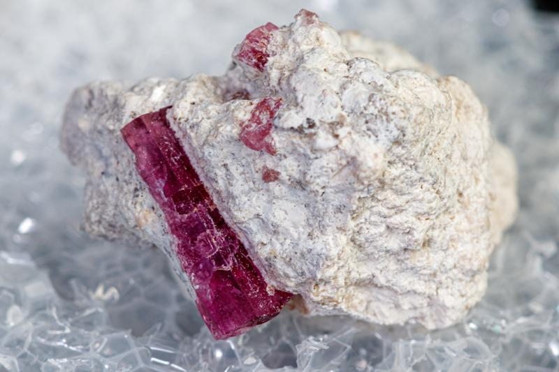 macro mineral stone red beryl on a black background close-up