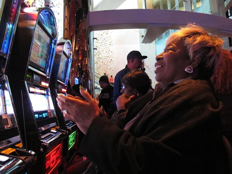 Lorraine Capers, of Brooklyn, N.Y., claps after winning seven free spins on a slot machine at the new $2.4 billion Revel casino resort moments after it opened in Atlantic City, N.J., on Monday, April 2, 2012. (AP Photo/Wayne Parry)