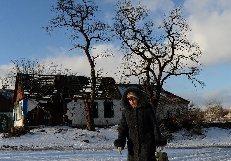 A woman walks past a building destroyed by fighting between pro-Russia and Ukrainian forces in the village of Stepanivka, eastern Ukraine, on December 30, 2014 (AFP Photo/Vasily Maximov)