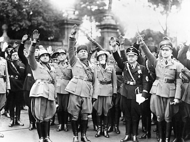 FILE - This Oct. 28, 1936 file photo shows Benito Mussolini, second from left, flanked by Nazis officers on the occasion of the celebration of the fourteenth anniversary of Italian Fascism. Not since Benito Mussolini's ignominious fall after failed attempts at making Italy a colonial power that gave Hitler the upper hand in their axis, has the executed former dictator's image carried such currency. (AP Photo, File)