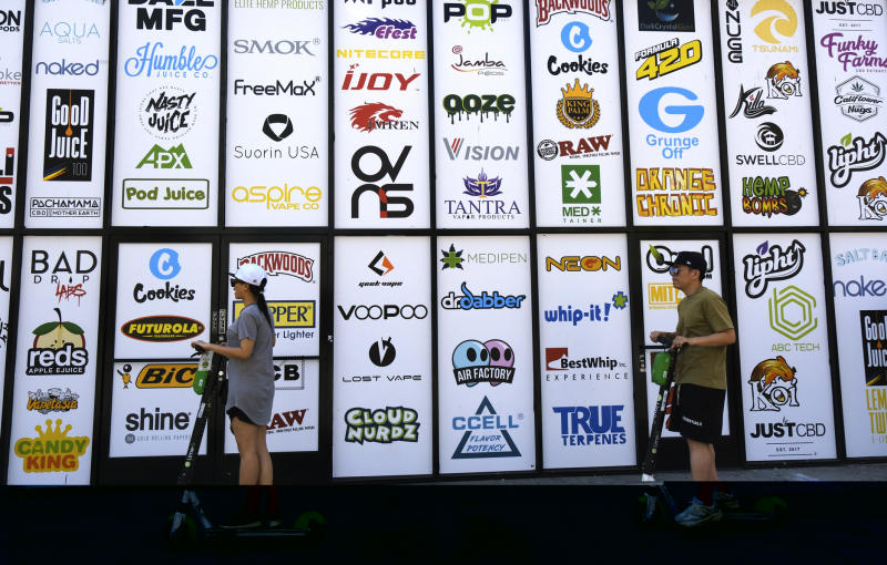 "FILE - This Aug. 28, 2019, file photo shows advertising logos for different cannabis brands posted on the side of a shop on a street lined with wholesale cannabis vape shops in downtown Los Angeles. The vape cartridges that go by the catchy, one-syllable name ""Dank"" - a slang word for highly potent cannabis - are figuring prominently in the federal investigation to determine what has caused a rash of mysterious and sometimes fatal lung illnesses apparently linked to vaping. The raw materials to produce a Dank vape aren't hard to find as you can order them from Chinese internet sites or buy the boxes and empty cartridges in shops in Los Angeles. (AP Photo/Richard Vogel, File)"