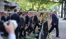 FILE PHOTO: FILE PHOTO: U.S. President Trump walks past a building defaced with graffiti by protestors in Washington