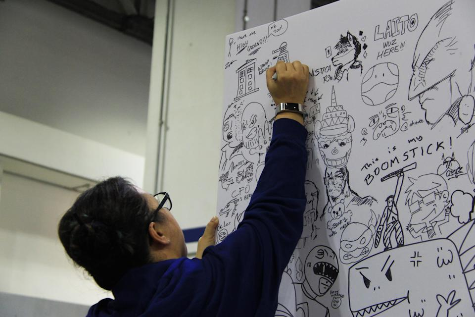 <p>A visitor drawing on a large doodle board at the Singapore Toy, Game and Comic Convention (STGCC) 2018 (PHOTO: Abdul Rahman Azhari/Yahoo Lifestyle Singapore) </p>