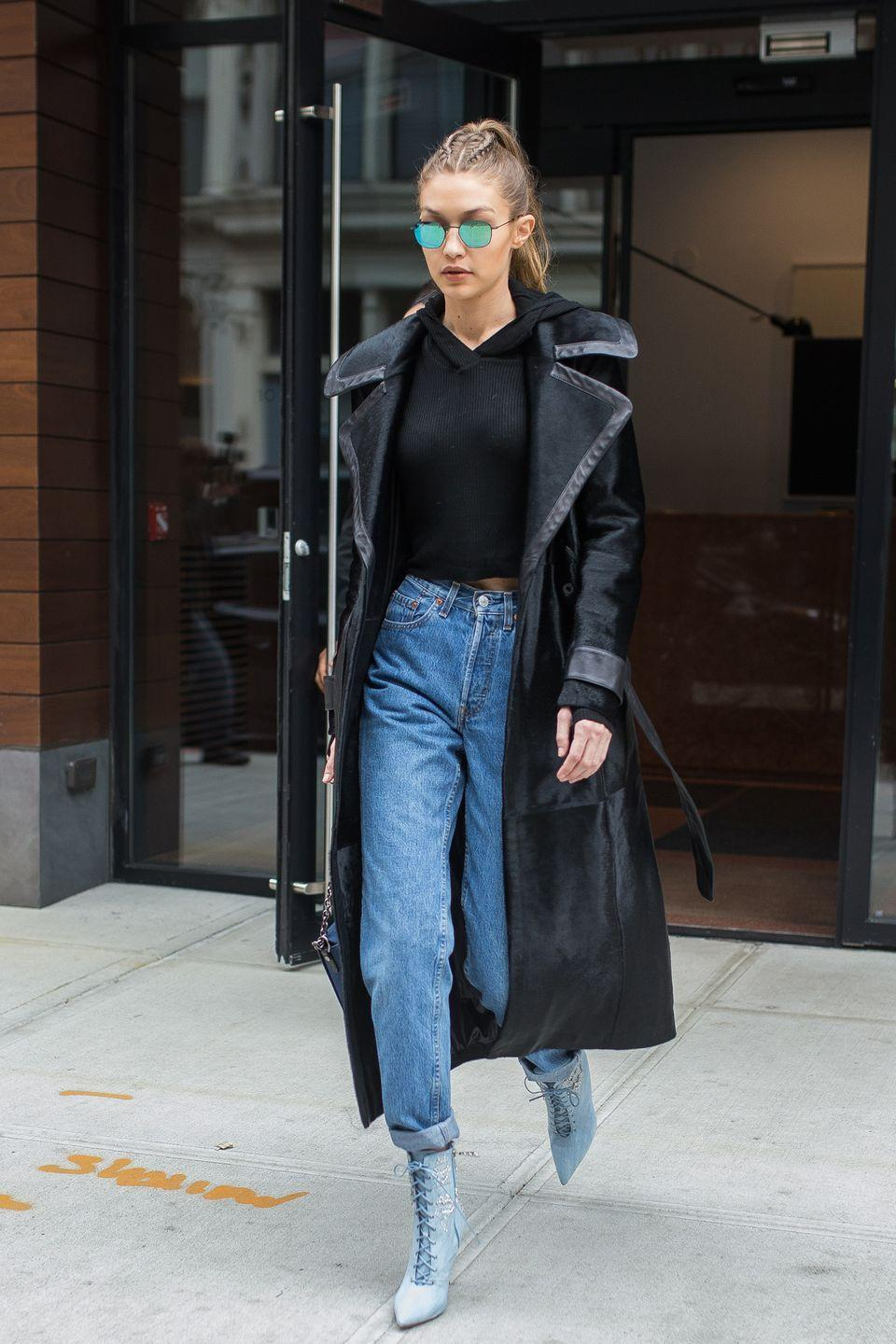 <p>In a black leather-lined coat, cropped hoodie, high-waited rolled jeans, Rihanna x Manolo lace-up ankle boots and reflective Krewe sunglasses while out in New York. </p>