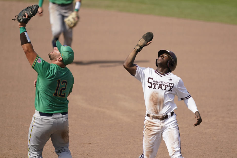 Notre Dame infielder Niko Kavadas (12) and Mississippi State base runner Brayland Skinner, right, look into the sun for a fly ball during an NCAA college baseball super regional game, Saturday, June 12, 2021, in Starkville, Miss. Mississippi State won 9-8. (AP Photo/Rogelio V. Solis)