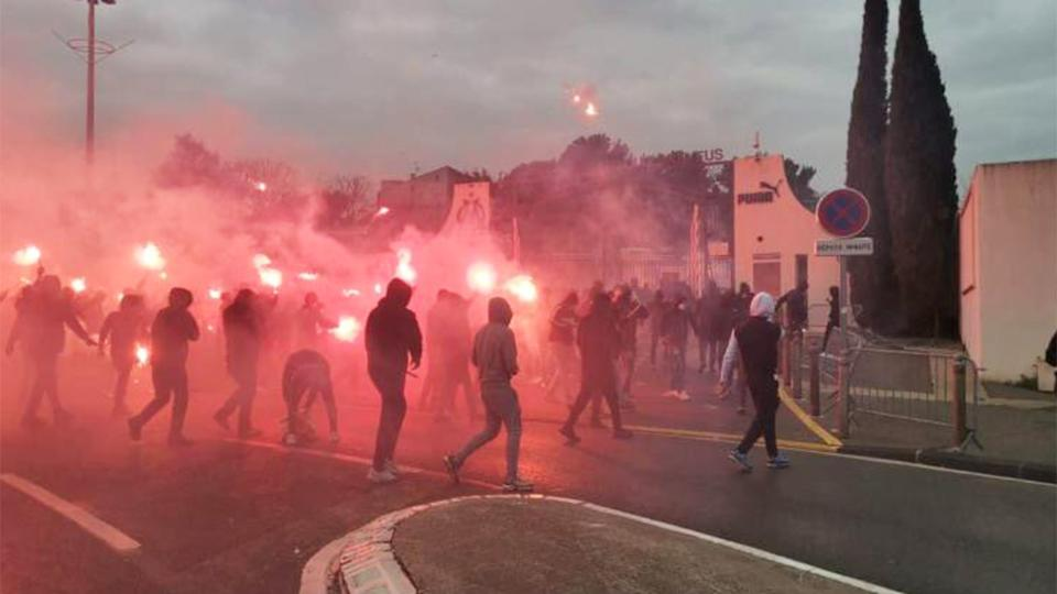 Marseille fans lighting flares storming the club grounds in anger.