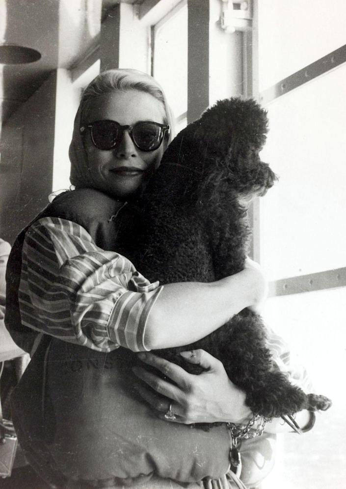 <p>The actress wears a life preserver as she endures the transatlantic voyage to Monaco. The actress was accompanied by her parents and French poodle, Oliver, who was a wedding gift from Cary Grant. </p>