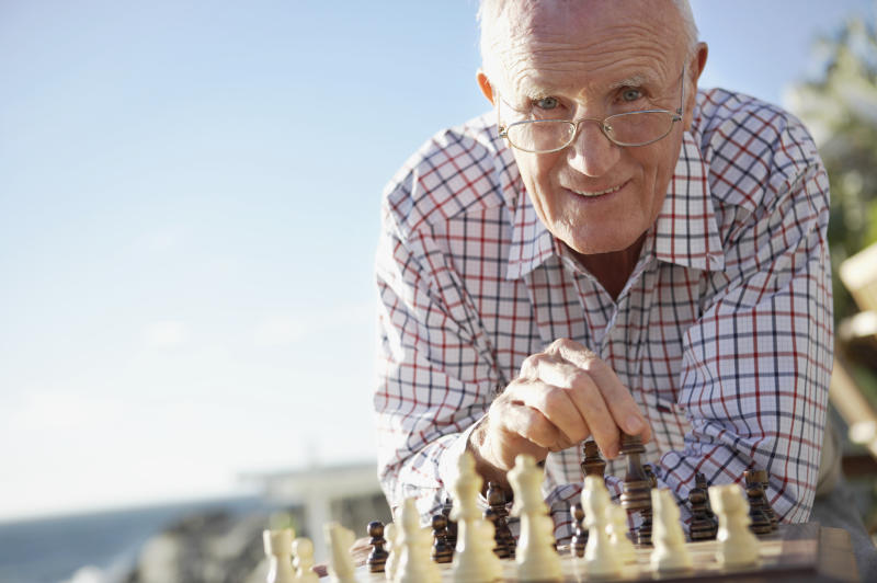 A smiling elderly man playing chess near the beach.
