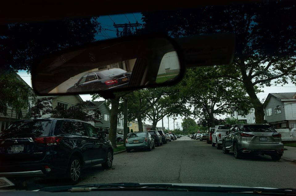 A tree-lined street is seen through the front window of a car.