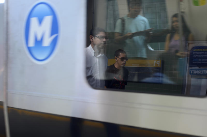 """Commuters are reflected in a subway car window in the Rio de Janeiro suburb of Iraja, Brazil, Wednesday, June 26, 2013. The Cavalcantes, residents of Iraja, say they must elbow their way onto packed public transit every morning and drill the children on how to react in case of a carjacking or armed robbery because, Paulo Cavalcante figures, """"it's only a matter of time before the violence that's all around us comes knocking on our door."""" (AP Photo/Nicolas Tanner)"""
