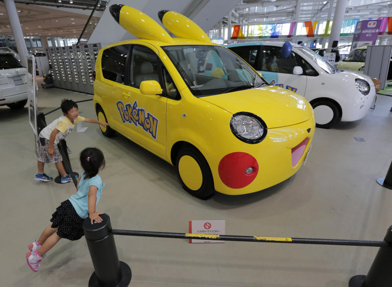 """Children look at Toyota's """"Porte,"""" decorated as a popular anime character Pokemon at a Toyota's showroom in Tokyo, Friday, Aug. 3, 2012. Toyota said April-June profit zoomed to 290.3 billion yen ($3.7 billion) from 1.1 billion yen on a jump in global sales as the Japanese automaker makes a comeback from a disaster plagued 2011. (AP Photo/Itsuo Inouye)"""