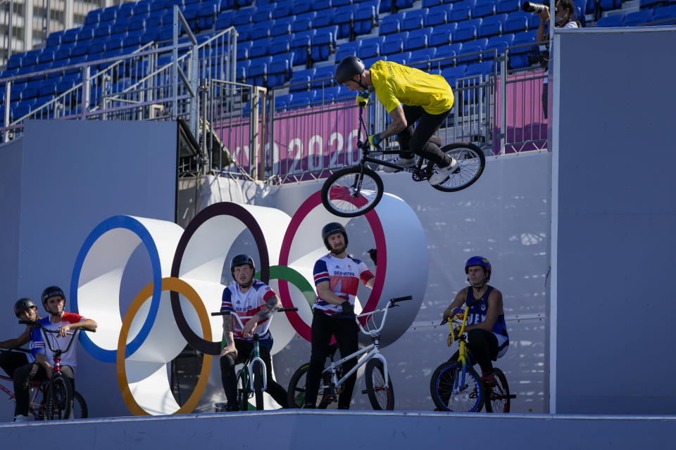Logan Martin of Australia makes a jump as other competitors watch during a BMX Freestyle training session at the 2020 Summer Olympics, Tuesday, July 27, 2021, in Tokyo, Japan. (AP Photo/Ben Curtis)