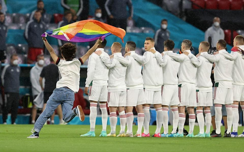 Pitch invader as players line up during the national anthems before the match - Reuters