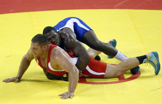 Cuba's Mijain Lopez, right, wrestles with Russia's Khasan Baroev during their gold medal bout in the 120 kilogram division of the greco-roman wrestling competition at the Beijing 2008 Olympics in Beijing Thursday, Aug. 14, 2008. Lopez won the gold medal. (AP Photo/Ed Wray)