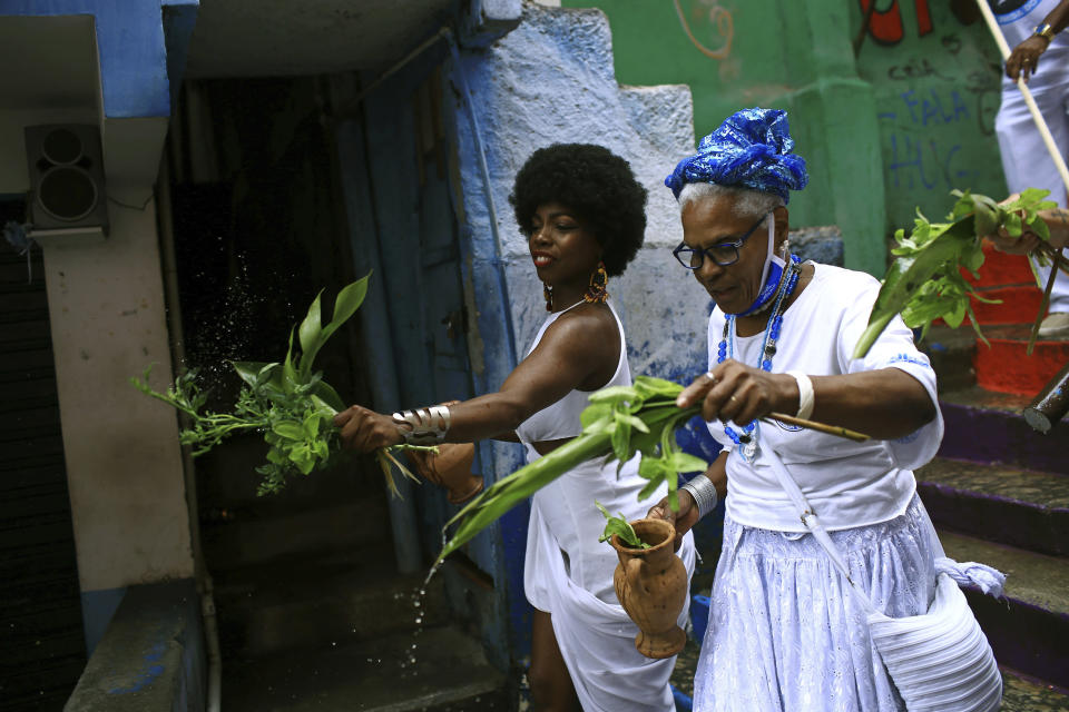 """Members of the Mocidade Unida do Santa Marta samba school perform a washing ritual for good luck called """"Lavagem"""" as they attend a ceremony marking Black Consciousness Day in the Santa Marta favela of Rio de Janeiro, Brazil, Friday, Nov. 20, 2020. Brazilians celebrate the holiday with Afro-Brazilian dance, music and religious ceremonies, reflecting the deep cultural and social ties of the Black community to the country's history and honor legendary anti-slave leader Zumbi dos Palmares on the day of his death. (AP Photo/Bruna Prado)"""