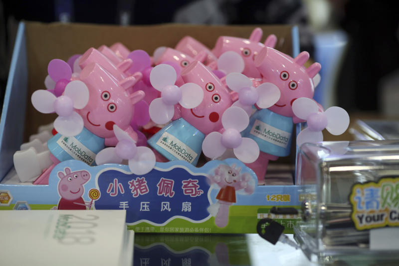 """In this April 27, 2018 photo, hand cranked fans with Peppa Pig theme are seen during the Global Mobile Internet Conference (GMIC) in Beijing, China. The cherubic British cartoon character, Peppa Pig, has become an unlikely target of China's censors as online fans use her porcine likeness in sardonic memes and """"gangster"""" catchphrases. (AP Photo/Ng Han Guan)"""