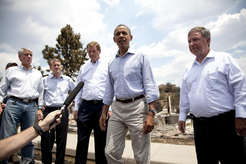 "President Barack Obama talks with media as he tours the Mountain Shadow neighborhood devastated by wildfires, Friday, June 29, 2012, in, Colorado Springs, Colo. From left, Sen. Mark Udall, D-Colo., Sen. Michael Bennet, D-Colo. Colorado Springs Mayor Steve Bach, President Barack Obama, and Rep. Doug Lamborn, R-Colo. After declaring a ""major disaster"" in the state early Friday and promising federal aid, President Obama got a firsthand view of the wildfires and their toll on residential communities. More than 30,000 people have been evacuated in what is now the most destructive wildfire in state history. (AP Photo/Carolyn Kaster)"