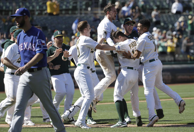 Oakland Athletics' Chad Pinder, second from right, is congratulated by teammates after driving in the winning run against the Texas Rangers during the ninth inning of a baseball game in Oakland, Calif., Wednesday, April 24, 2019. (AP Photo/Jeff Chiu)